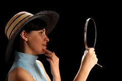Jonge vrouw die met strohoed spiegel bekijkt stock foto's