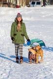 Jonge vrouw die met twee de Amerikaanse Pit Bull Terrier winter lopen Royalty-vrije Stock Afbeeldingen
