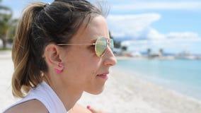 Jonge vrouw die met zonnebril op zandig strand zitten stock footage