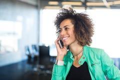 Jonge vrouw die mobiele telefoon in bureau met behulp van Royalty-vrije Stock Afbeelding