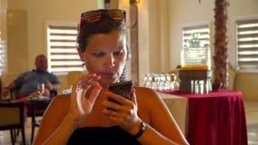 Jonge vrouw die mobiele telefoon in koffie bekijken Het wachten op controle stock footage