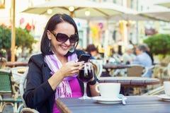 Jonge vrouw die mobiele telefoon met behulp van terwijl het ontspannen in koffie Royalty-vrije Stock Foto's