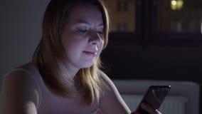 Jonge vrouw die mobiele telefoon op het bed met behulp van vóór zij slaap bij nacht Mobiel verslaafdenconcept stock footage