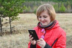 Jonge vrouw die mobiele telefoon in openlucht met behulp van Een jonge vrouw die het smartphonescherm bekijken terwijl in openluc royalty-vrije stock afbeeldingen