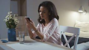 Jonge vrouw die mobiele telefoon thuis met behulp van stock video