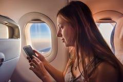 Jonge vrouw die mobiele telefoon in vliegtuig met behulp van bij zonsondergang Stock Afbeeldingen