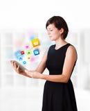 Jonge vrouw die moderne tablet met kleurrijke pictogrammen bekijken Royalty-vrije Stock Foto's