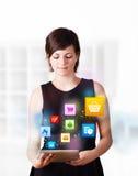 Jonge vrouw die moderne tablet met kleurrijke pictogrammen bekijken Stock Foto's