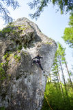 Jonge vrouw die moeilijke rots in bos beklimmen Stock Foto's
