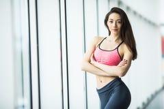 Jonge vrouw die na training bij gymnastiek dichtbij venster rusten Geschiktheidswijfje die onderbreking na opleidingssessie in ge royalty-vrije stock afbeeldingen