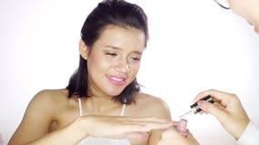 Jonge vrouw die nagellak in salon toepassen stock videobeelden