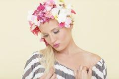 Jonge vrouw die neer met bloemen in haar haar kijkt stock afbeelding