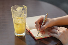 Jonge vrouw die nota neemt Het schrijven met pen in notitieboekje bij de koffie Royalty-vrije Stock Foto's