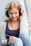 Jonge vrouw die nota's neemt die aan muziek luisteren Royalty-vrije Stock Afbeelding