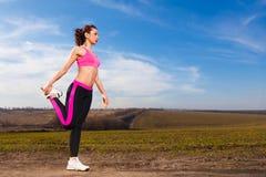 Jonge vrouw die oefeningen op blauwe hemelachtergrond doen Royalty-vrije Stock Foto