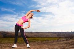 Jonge vrouw die oefeningen op blauwe hemelachtergrond doen Royalty-vrije Stock Fotografie