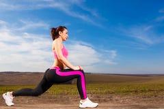 Jonge vrouw die oefeningen op blauwe hemelachtergrond doen Stock Afbeeldingen