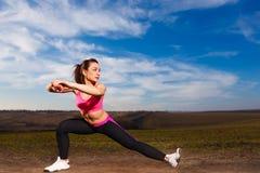 Jonge vrouw die oefeningen op blauwe hemelachtergrond doen Royalty-vrije Stock Foto's