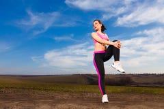 Jonge vrouw die oefeningen op blauwe hemelachtergrond doen Royalty-vrije Stock Afbeelding