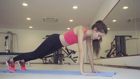 Jonge vrouw die oefeningsplank in gymnastiek doen Het meisje spant spieren van buikpers stock video