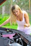 Jonge vrouw die olieniveau in de auto controleert stock afbeelding