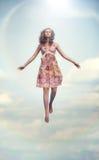 Jonge vrouw die omhoog vliegt Stock Afbeeldingen