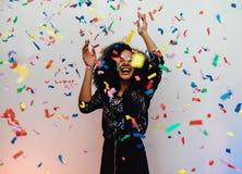 Jonge vrouw die onder confettien thuis dansen royalty-vrije stock afbeelding