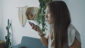Jonge vrouw die onderaan haar mobiele telefoon gillen stock footage