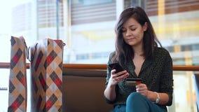 Jonge vrouw die online aankopen maakt die creditcard en telefoon met behulp van stock video