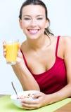 Jonge vrouw die ontbijt hebben thuis stock foto's