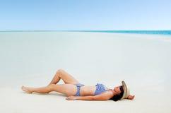 Jonge vrouw die op Aitutaki-Lagune Cook Islands zonnebaden Stock Afbeeldingen