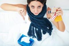 Jonge vrouw die op bed liggen en de pillen van de geneeskundeblaar houden Royalty-vrije Stock Foto