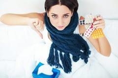 Jonge vrouw die op bed liggen en de pillen van de geneeskundeblaar houden Stock Foto