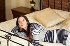 Jonge vrouw die op bed ligt stock afbeelding