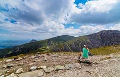 Jonge vrouw die op bergspoor rusten stock foto