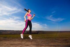 Jonge vrouw die op blauwe hemelachtergrond springen Royalty-vrije Stock Fotografie