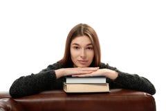 Jonge vrouw die op boeken leunen Royalty-vrije Stock Foto's