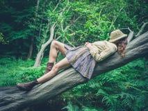 Jonge vrouw die op boom in bos liggen Stock Foto