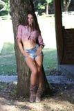 Jonge vrouw die op boom leunen royalty-vrije stock afbeelding