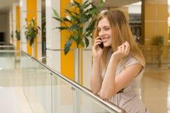 Jonge vrouw die op cellphone in de wandelgalerij spreekt Stock Afbeeldingen