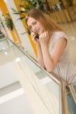Jonge vrouw die op cellphone in de wandelgalerij spreekt Stock Foto's