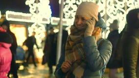 Jonge vrouw die op celtelefoon bij de markt van de Kerstmisstraat spreken stock video