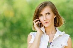 Jonge vrouw die op celtelefoon spreekt Royalty-vrije Stock Foto's
