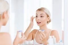 Jonge vrouw die op contactlenzen bij badkamers zetten stock foto's