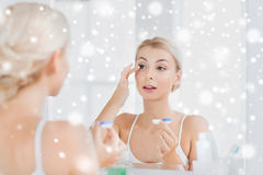 Jonge vrouw die op contactlenzen bij badkamers zetten Royalty-vrije Stock Fotografie