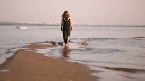 Jonge vrouw die op de benen van een het waterlijn van de kustlijn lopen stock video