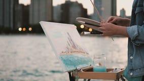 Jonge vrouw die op de kust van het meer van Michigan in Chicago, Amerika trekken Lichten van de stad in op achtergrond stock videobeelden