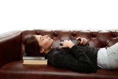 Jonge vrouw die op de laag met boeken onder zijn hoofd liggen Stock Foto's