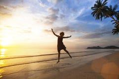 Jonge vrouw die op de overzeese kust tijdens de verbazende zonsondergang springen Stock Fotografie