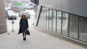 Jonge vrouw die op de straat loopt stock footage